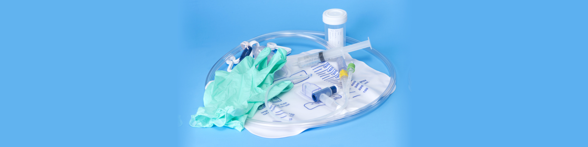 Foley catheter and drainage bag with sterile gloves and specimen container on blue background
